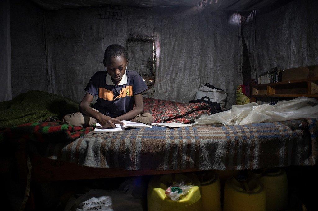 肯尼亚首都内罗毕,一名11岁的男孩正在翻阅六年级的课本,校对习题答案。因为家中没有电脑手机,他无法参加线上教学。
