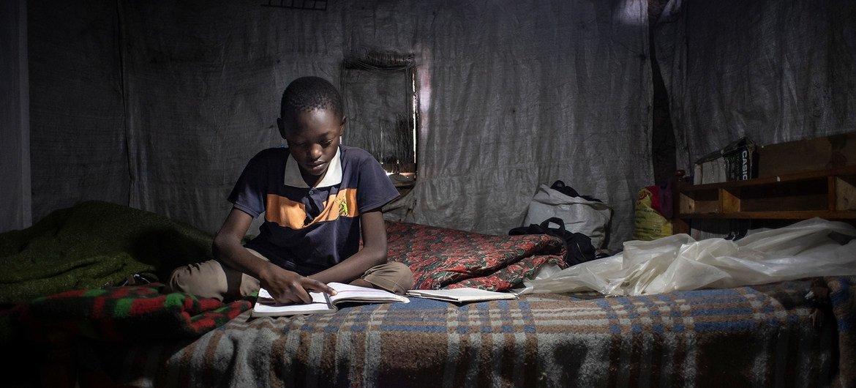 Un enfant de 11 ans étudie ses manuels de classe et révise les exercices chez lui à Nairobi, au Kenya. Il ne peut pas participer à l'apprentissage en ligne car sa famille n'a pas de téléphone portable.