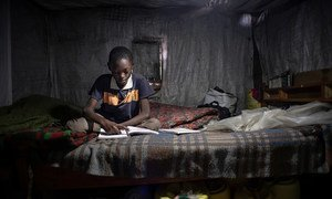 An 11-year-old child studies his Class 6 textbooks and revises the exercises at home in Nairobi, Kenya. He cannot participate in online learning as his family has no mobile phone.