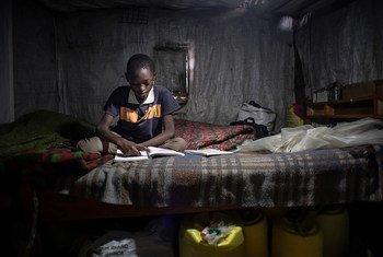 Criança de 11 anos resolve exercícios em casa em Nairóbi, Quênia. Ele não pode participar do aprendizado online porque sua família não tem um telefone celular.