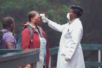 Une fonctionnaire d'un parc en Tanzanie mesure la température corporelle d'une touriste dans le cadre d'une procédure opérationnelle visant à contrer la Covid-19.