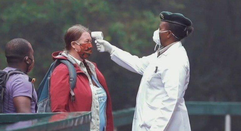 Пандемия нанесла сокрушительный удар по туризму. На снимке - сотрудница парка в Танзании измеряет температуру у туристов.