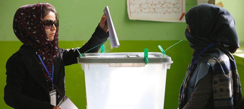 امرأة تدلي بصوتها في الانتخابات البرلمانية في أفغانستان في مركز اقتراع في كابول عام 2018.
