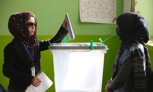 A woman casts her vote in Afghanistan's parliamentary elections at a Kabul polling centre in 2018.