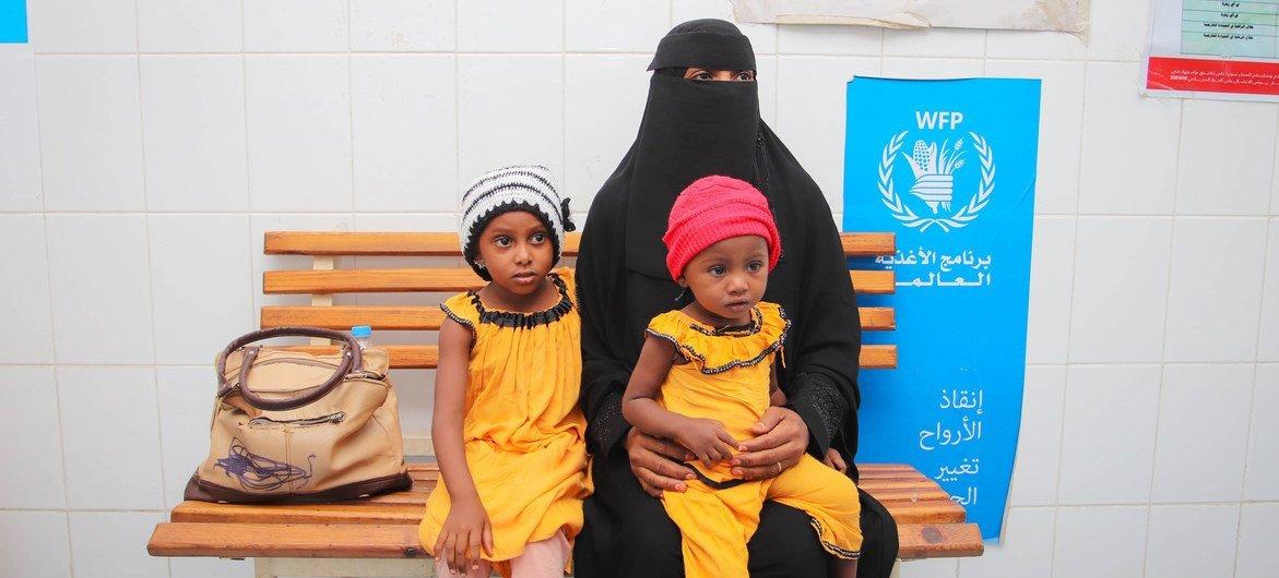 أم تزور أحد المرافق الصحية في اليمن لتلقي العلاج لابنتها الصغيرة (ترتدي قبعة حمراء) التي تعاني من سوء التغذية.