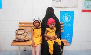 Una mujer con sus dos hijos en un centro de salud de Yemen. La niña del gorro rojo necesita tratamiento por desnutrición.