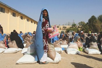 People receive food rations at a WFP distribution site on the outskirts of Herat in Afghanistan.