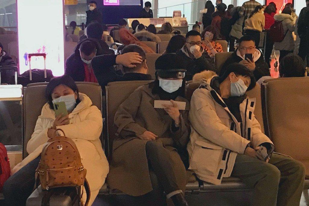 在中国深圳宝安国际机场的等候区,人们戴着口罩。