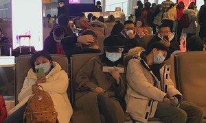 Personas con tapabocas para protegerse del coronavirus esperan para salir del Aeropuerto Internacional de Shenzhen Bao en China.