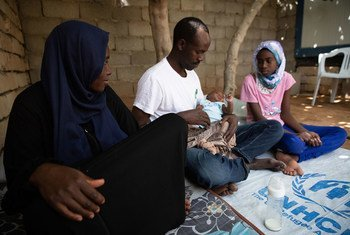 Abdulmajeed and wife Halima, Sudanese refugees from Darfur, sit with their two daughters at home in Tripoli, Libya.