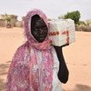 A South Sudanese refugee receives soap from a UNHCR distribution centre at a settlement in South Darfur.