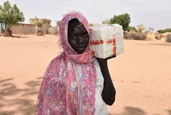 Une réfugiée sud-soudanaise reçoit du savon d'un centre de distribution du HCR dans un camp du Sud Darfour.