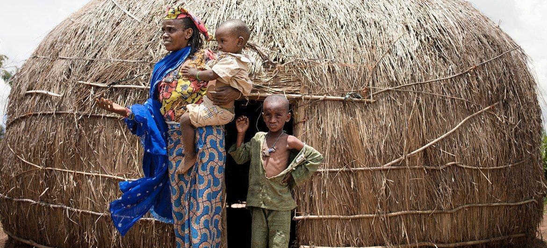 امرأة وأبناؤها الصغار يقفون أمام مأواهم في مخيم للنازحين في بابوا، جمهورية أفريقيا الوسطى.