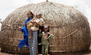 A woman and her young sons stand in front of their shelter in a camp for displaced people in Baboua, Central African Republic.