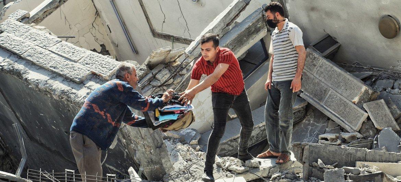 إنقاذ ما يمكن إنقاذه من الممتلكات من تحت أنقاض أحد المباني المدمرة في قطاع غزة بسبب الغارات الإسرائيلية في أيار/مايو 2021.
