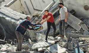 إنقاذ ما يمكن إنقاذه من تحت أنقاض أحد المباني المدمرة في قطاع غزة بسبب الغارات الإسرائيلية في أيار/مايو 2021.
