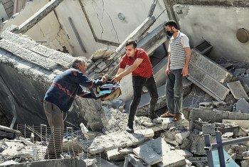 Люди пытаются вынести личные вещи из разрушенного жилого здания в Газе. Май 2021 года.