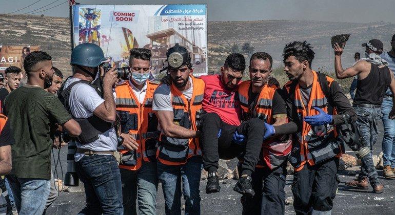 عاملو إغاثة يساعدون رجلا أصيب في رام الله بالضفة الغربية.
