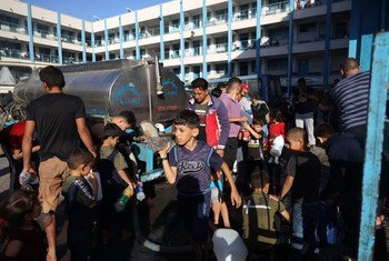 Children in Gaza gather at a water truck to fill bottles with clean drinking water.