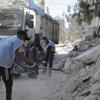 عمال الأونروا يعملون على إزالة الأنقاض في غزة.