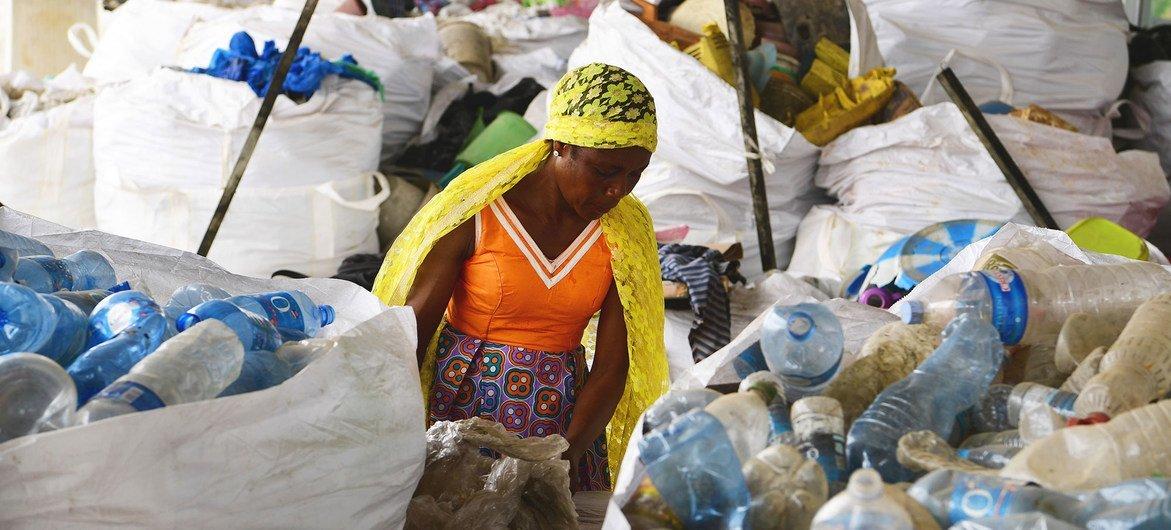 Una mujer examina bolsas de plástico desechadas en Côte d'Ivoire.