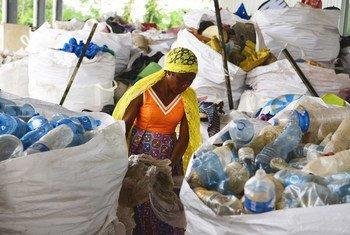 Une femme trie des sacs plastiques en Côte d'Ivoire.