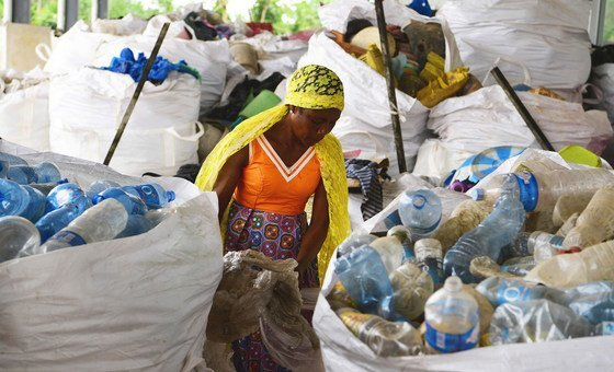 A woman sorts through bags of discarded plastic in Côte d'Ivoire.
