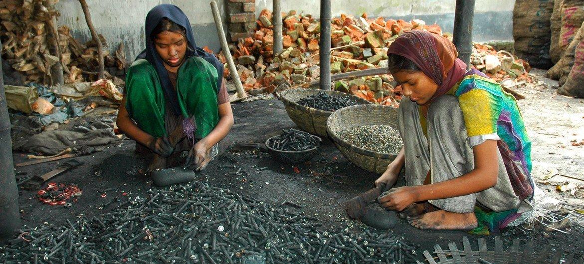 बांग्लादेश के ढाका शहर की एक कार्यशाला में बैटरियों से निकली धातु को री-सायकिल करती दो लड़कियाँ.