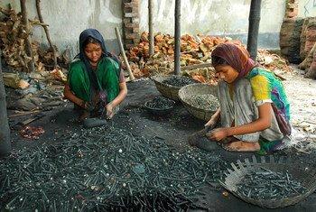 Wasichana wawili wanakata chuma kutoka kwa betri zilizotumiwa huko Dhaka, Bangladesh.