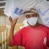 Trabajador humanitario carga un costal de frijol del almacén de distribución de comida del Programa Mundial de Alimentos en Sana´a, Yemen.
