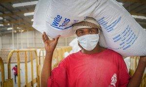 عامل يحمل كيساً من الفاصولياء في مستودع توزيع الأغذية التابع لبرنامج الأغذية العالمي في صنعاء، اليمن.