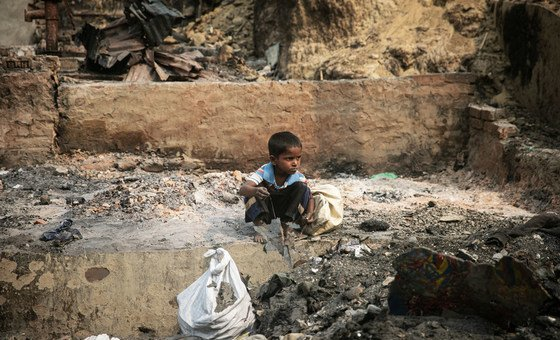 A child rummages through debris after a massive fire devastated the Balukhali area of the Rohingya refugee camps in Cox's Bazar.