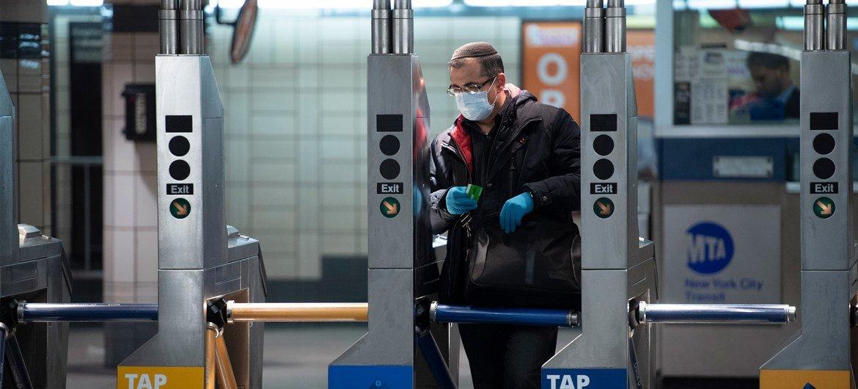 न्यूयॉर्क के सबवे सिस्टम में ट्रेन पकड़ने के लिए मास्क और दस्ताने पहनकर प्रवेश करता एक व्यक्ति.