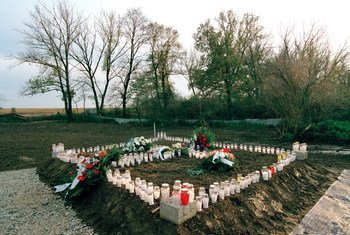 Candles and wreaths mark a mass grave site at Ovcara, Croatia, where approximately 200 civilians were massacred in 1994.