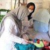 अफ़ग़ानिस्तान के दाईकुण्डी में, एक पारिवारिक स्वास्थ्य केन्द्र में एक बच्चे की स्वास्थ्य जाँच-पड़ताल करते हुए एक दाई.