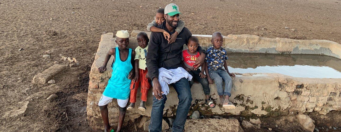 UN News' Abdelmonem Makki and his nephews in the village where he was raised in South Darfur, Sudan.