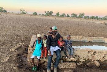 El redactor de Noticias ONU Abdelmonem Makki y sus sobrinos en la población en la que se crió en el sur de Darfur, en Sudán.
