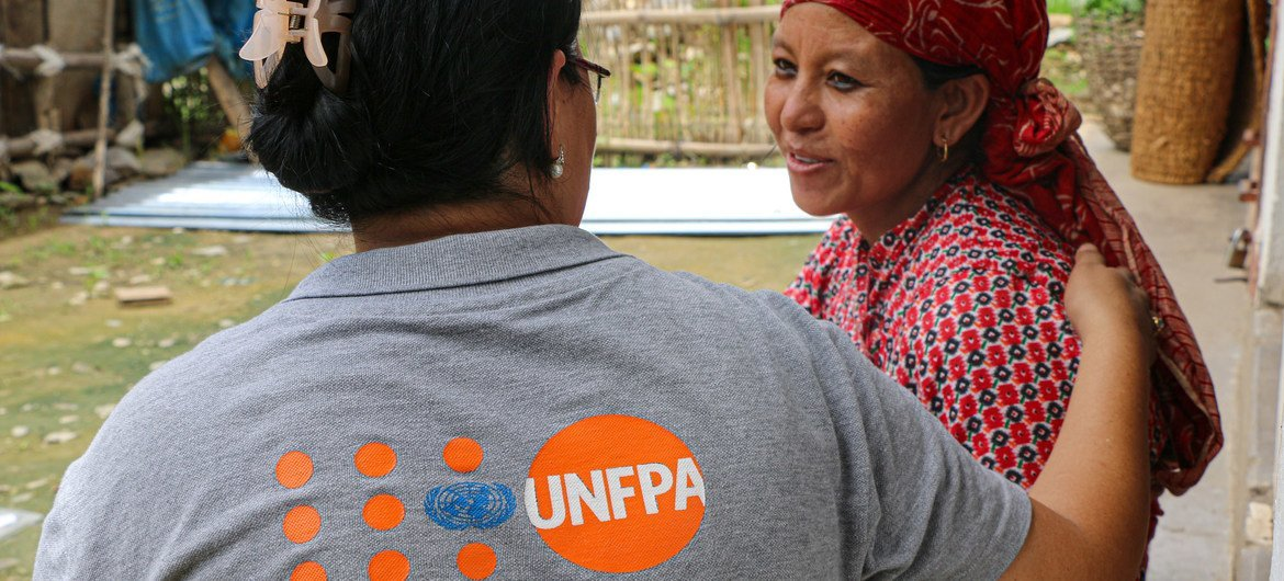 A UNFPA staff member speaks with a new mother cradling her child (not pictured), who were affected by the devastating 2015 earthquakes in Nepal. (file photo)