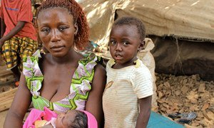A refugee mother from Central African Republic sits with her children beside a makeshift shelter in Ndu village, the Democratic Republic of the Congo.