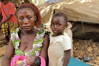Une mère réfugiée de République centrafricaine est assise avec ses enfants à côté d'un abri de fortune dans le village de Ndu, en République démocratique du Congo.