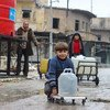Young boys collect water from UNICEF-supported a water point in east Aleppo City in Syria.
