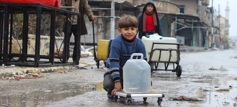 (من الأرشيف) صبية صغار يجمعون المياه من نقطة مياه تدعمها اليونيسف في شرق مدينة حلب في سوريا .