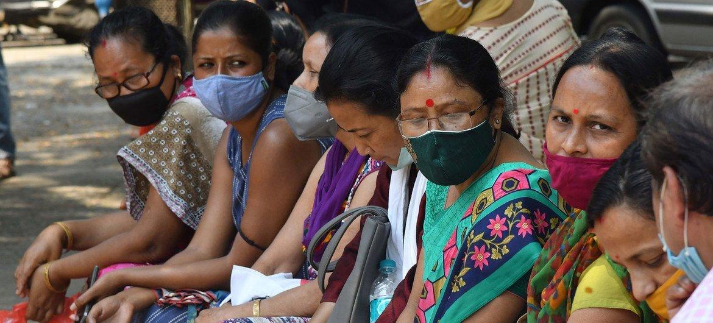 भारत के गुवाहाटी शहर में कोविड-19 टीकाकरण के लिये स्वास्थ्य केन्द्र के बाहर इन्तज़ार कर रहे लोग.