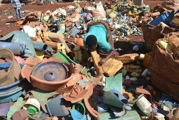 Nchini Uganda, mwanamke mkazi wa Hoima akichambua plastiki kabla ya kurejelezwa.