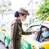 泰国曼谷,一位女警正在为出租车司机测量体温。