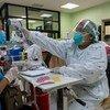 थाईलैण्ड के नोन्थाबुरी प्रांत में एक स्वास्थ्यकर्मी एक मरीज़ के तापमान की जाँच कर रही है.