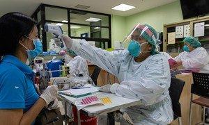 Una trabajadora de salud revisa la temperatura de una paciente en la provincia de Nonthaburi, en Tailandia.