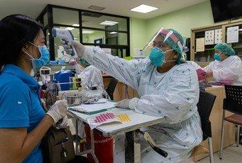 Un agent de santé vérifie la température d'une patiente dans un hôpital de la province de Nonthaburi, en Thaïlande.