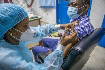 बेनिन में एक यूएन कर्मचारी को कोविड-19 वैक्सीन की ख़ुराक दी जा रही है.
