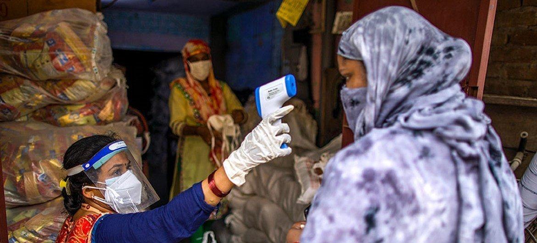 नई दिल्ली के एक राशन वितरण केंद्र पर एक महिला के तापमान की जाँच की जा रही है.